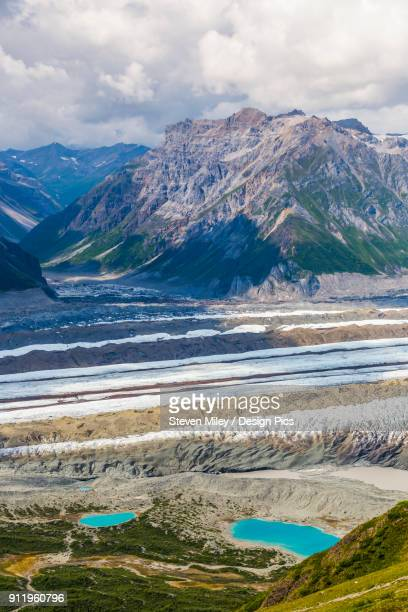 View of Kennicott Glacier and adjacent mountains in Wrangell-St. Elias National Park. Small colorful spots next to left-hand lake are tents