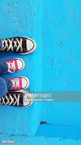 View Of Kids Foot Wearing Pink Canvas Between Another Foot On Blue Steps