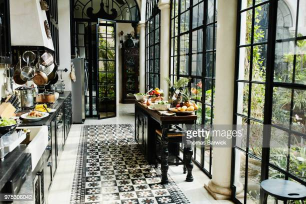 view of kitchen with sideboard filled with food for dinner party - domestic kitchen stock pictures, royalty-free photos & images