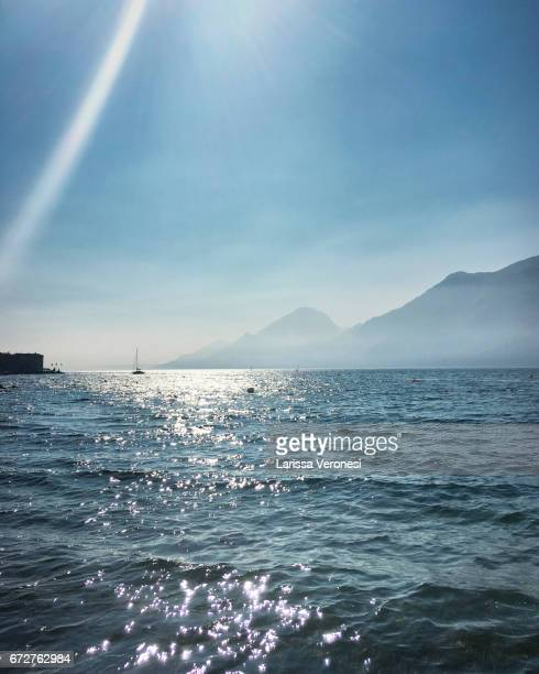 view of lake garda with sailboat, porto, brenzone sul garda - larissa veronesi stock pictures, royalty-free photos & images