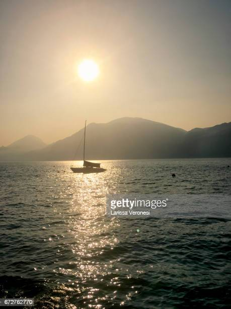view of lake garda with sailboats at sunset, brenzone sul garda - larissa veronesi stock pictures, royalty-free photos & images