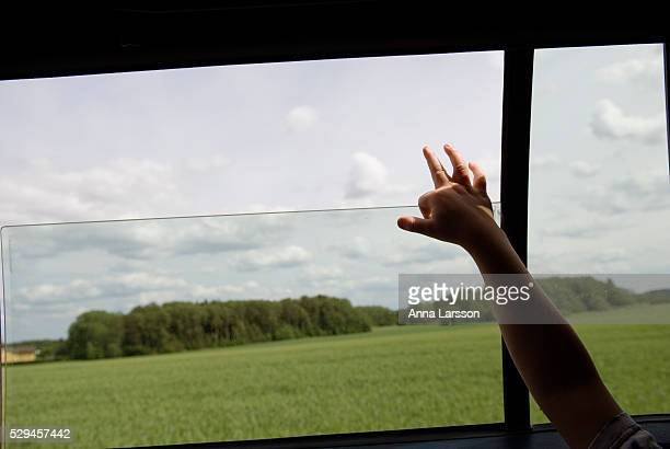 View of landscape through car window, child raising hand in car