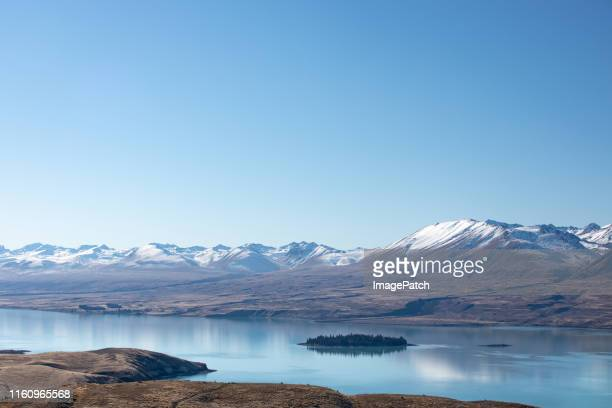 view of large lake surrounded by mountains in the southern alps of new zealand. - tékapo fotografías e imágenes de stock