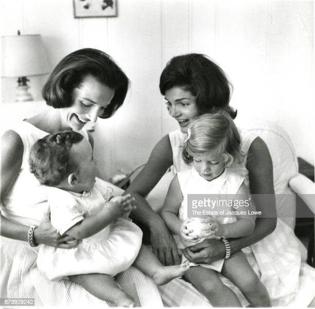 View of Lee Radziwill and her sister Jacqueline Kennedy , as they hold their children, Anthony and Caroline, Hyannis Port, Massachusetts, late 1950s...