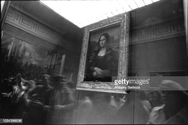 View of Leonardo da Vinci's 'Mona Lisa' portrait as museumgoers are reflected in the glass that protects the painting at the Louvre Paris France 1990s