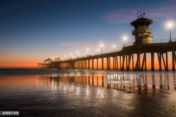 view of lighthouse at seaside during sunset - huntington beach stock pictures, royalty-free photos & images