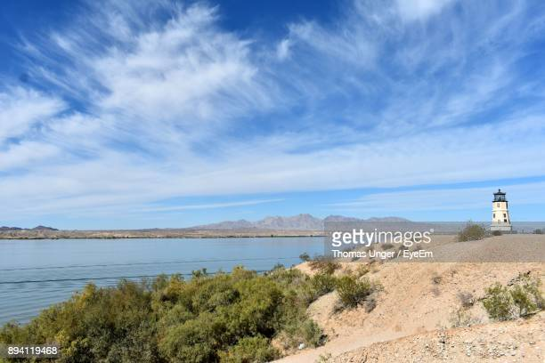 view of lighthouse on beach against cloudy sky - lake havasu stock photos and pictures