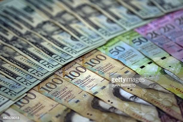 View of local currency and US dollar banknotes in Caracas on March 24 2014 The Venezuelan government postponed another week the entry into force of...