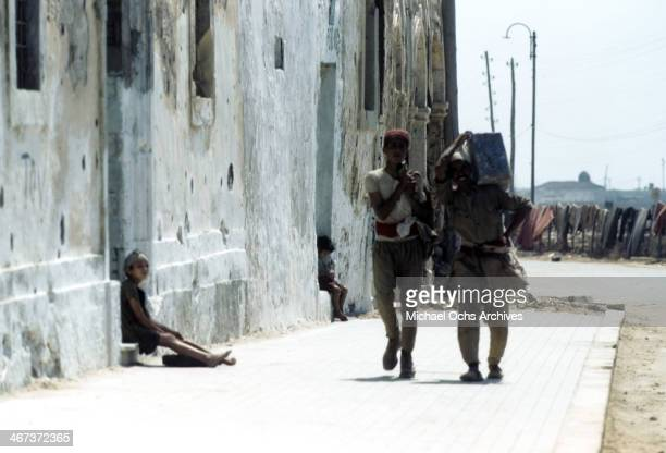 A view of local Libyanese boys wearing regional clothes walk down a sidewalk in Benghazi Libya