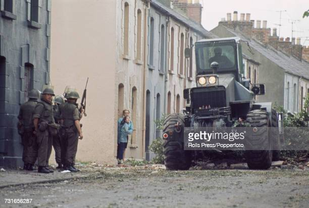 View of local residents standing in a doorway of a terraced house watched by soldiers as a British Army bulldozer clears away debris and rough...