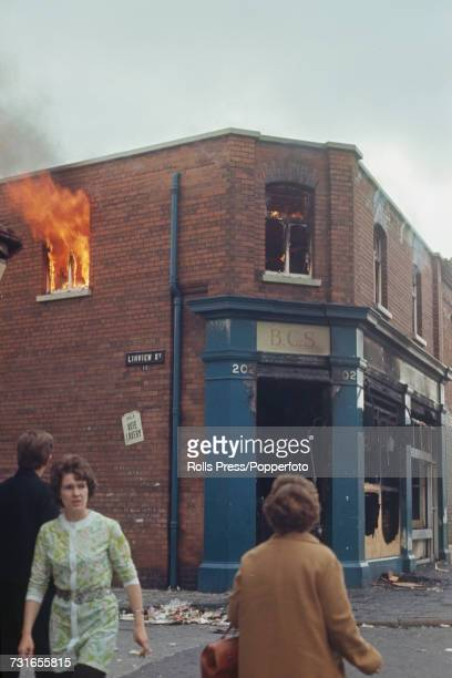 View of local residents walking past a burning fire damaged shop on the corner of Grosvenor Road and Linview Street in the predominantly Catholic...