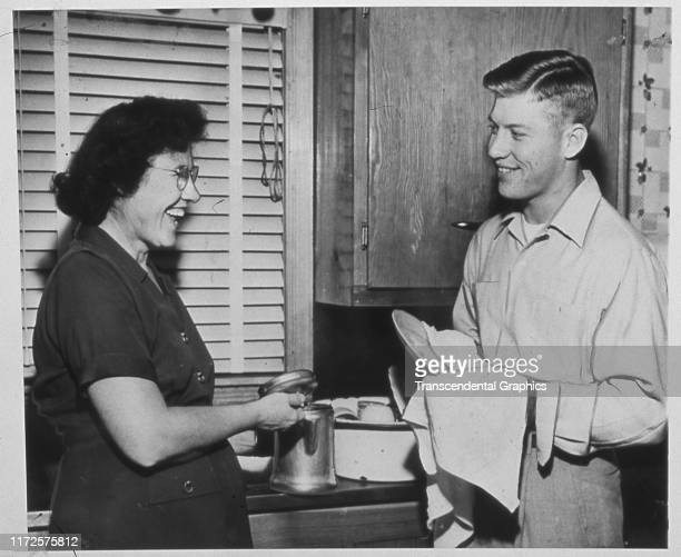 View of Lovell Mantle and her son, American baseball player Mickey Mantle , of the New York Yankees, as they wash dishes in the kitchen, Fischer,...