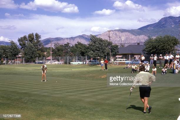 View of LPGA golfer Mickey Wright putting on the green at the Ogden Country Club in Ogden Utah June 1962 At right spectators cluster on a hill inside...