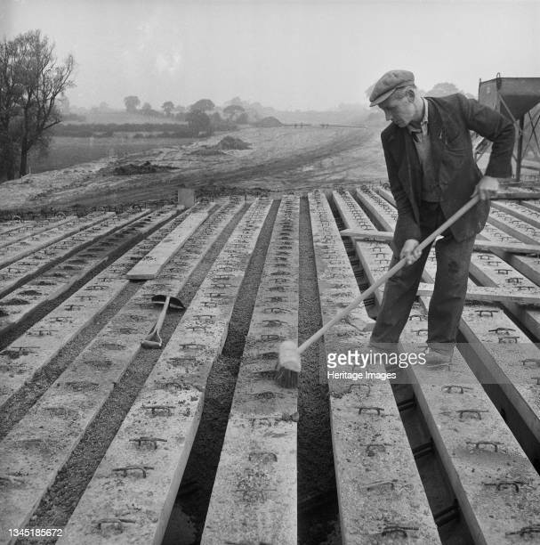 View of Lytag being used as infill on Bridge 360 during the construction of the Birmingham to Preston Motorway , showing a worker with a broom...