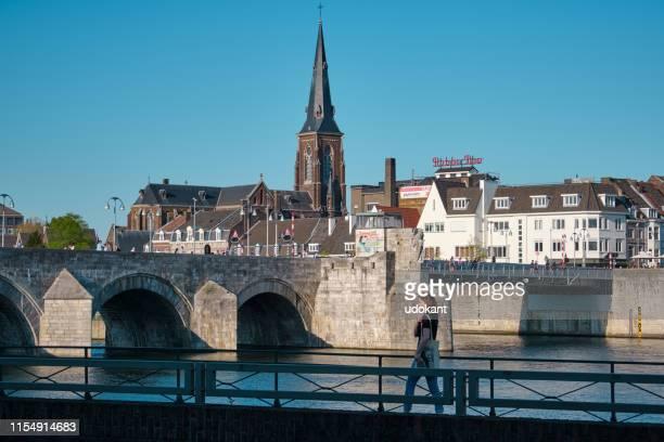 マーストリヒトのビュー。マース (ムーズ) 川の橋を渡って、教会の近くで女性が歩く - マーストリヒト ストックフォトと画像