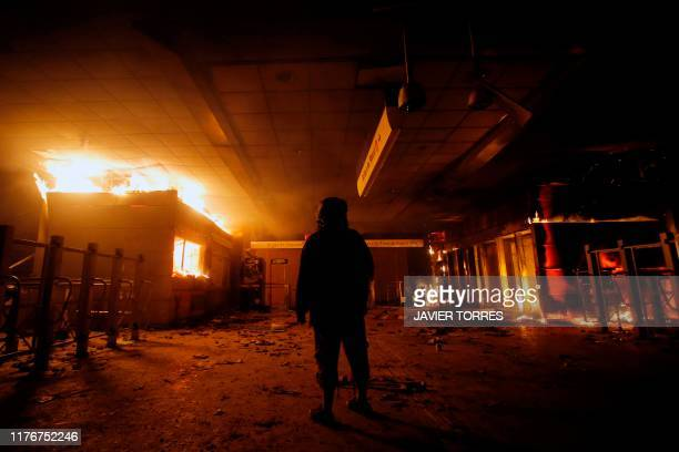 View of Macul Metro station set on fire by protesters during a mass faredodging protest in Santiago on October 19 2019 The entire Santiago Metro...
