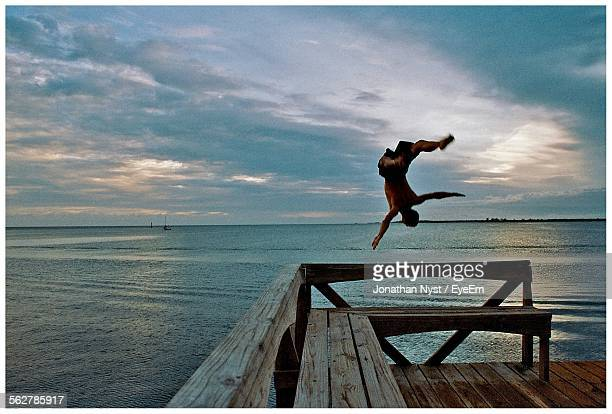 View Of Man Back Flipping From Pier Into Sea