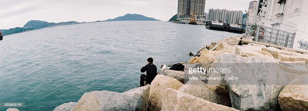 View Of Man Sitting On City Shore With Stones In Foreground : Foto stock