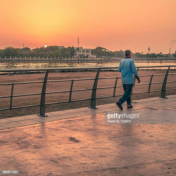 View Of Man Walking On Footpath During Sunset
