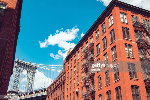 view of manhattan bridge from dumbo brooklyn against blue sky - brooklyn new york stock-fotos und bilder