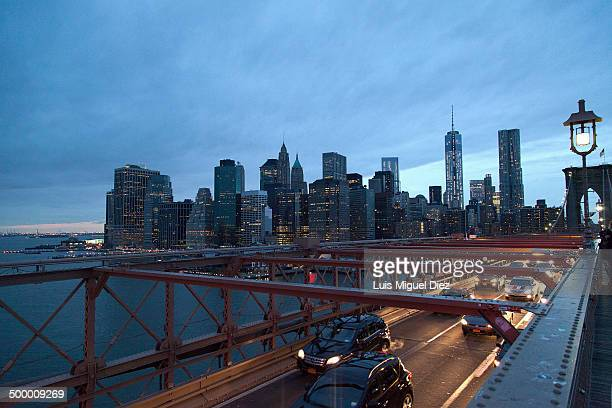 CONTENT] A view of Manhattan from the Brooklyn Bridge at dusk with a lamppost as a witness of the traffic in New York United States in 2013