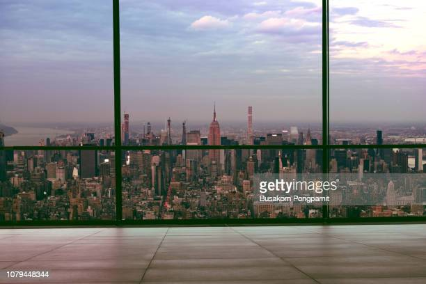 view of manhattan new york city skyline buildings from high rise window - beautiful expensive real estate overlooking empire state building and skyscrapers in gorgeous breathtaking penthouse cityscape - looking through window stock pictures, royalty-free photos & images