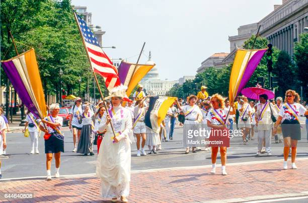 View of marchers among them one dressed as Carrie Chapman Catt who carries an American flag as they walk along Pennsylvania Avenue during a rally in...