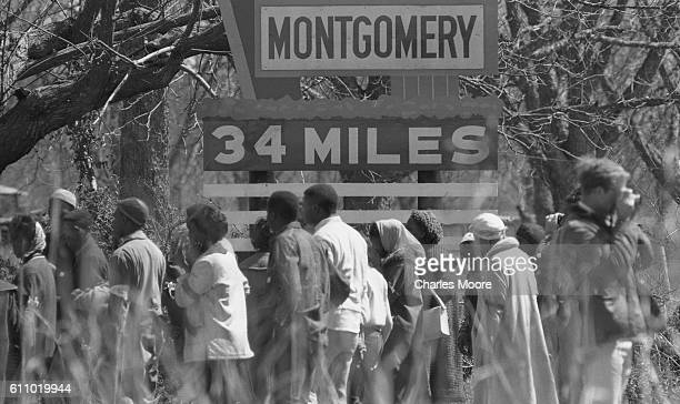 View of marchers as they pass a sign during the Selma to Montgomery March Alabama late March 1965 The sign 'Montgomery 34 Miles ' is 20 miles outside...