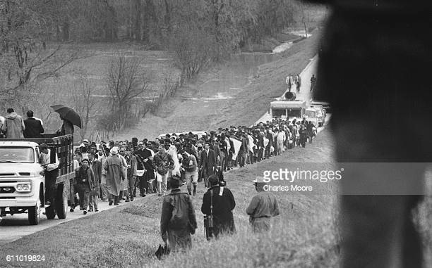 View of marchers as they walk along the highway during the Selma to Montgomery March Alabama late March 1965 Members of the press stand both beside...