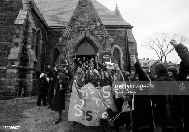 View of marchers at a feminist parade saluting with their arms raised high outside Old Cambridge Baptist Church on Massachussetts Avenue in Cambridge...