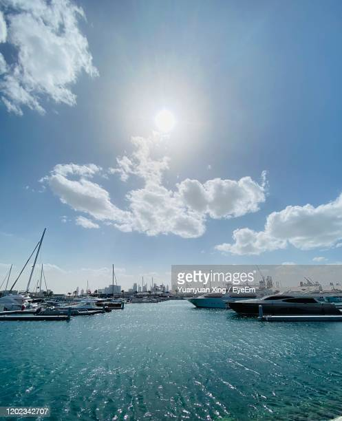 view of marina at harbor against cloudy sky - moored stock pictures, royalty-free photos & images