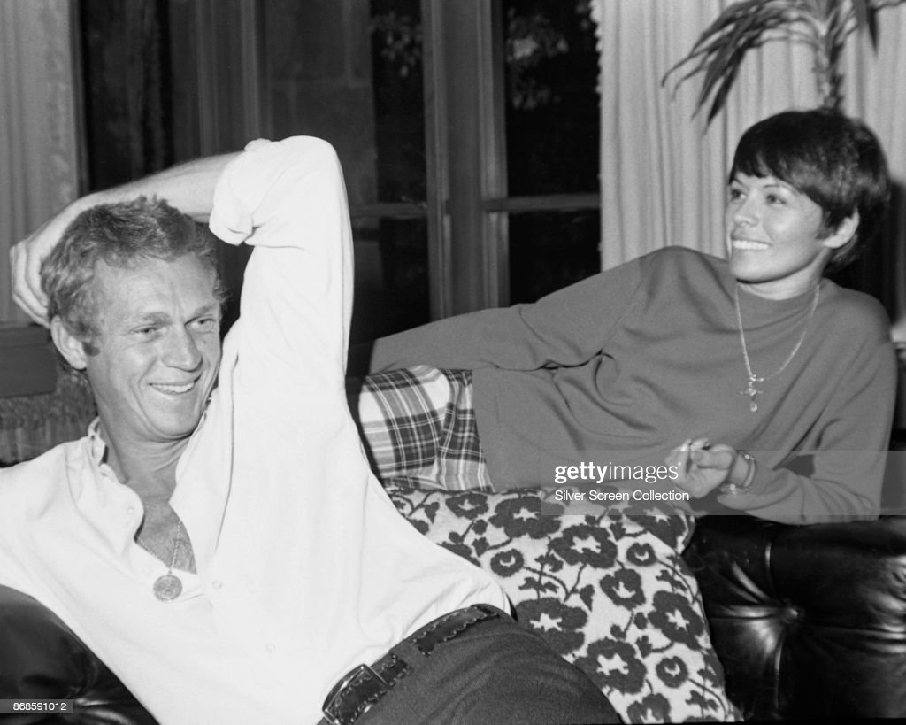View of married actors Steve McQueen (1930 - 1980) and Neile Adams as they share a laugh at home, Los Angeles, California, 1960s.
