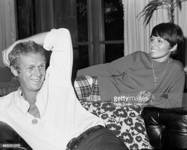 View of married actors Steve McQueen and Neile Adams as they share a laugh at home Los Angeles California 1960s