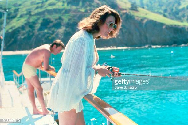 View of married American actors Natalie Wood with a fishing rod and Robert Wagner on their yacht the 'Splendour' October 8 1976