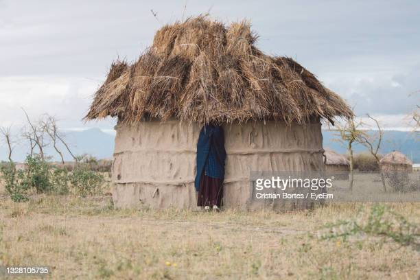 view of masai woman under cottage roof - bortes stock pictures, royalty-free photos & images