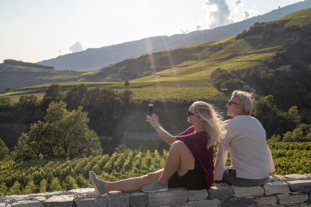 View of mature couple relaxing on wall near vineyard