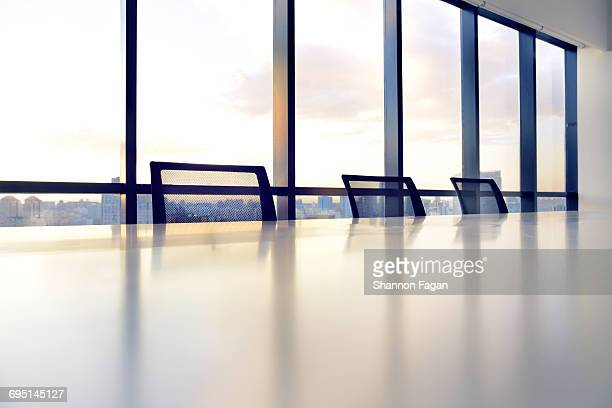 View of meeting room table chairs and cityscape