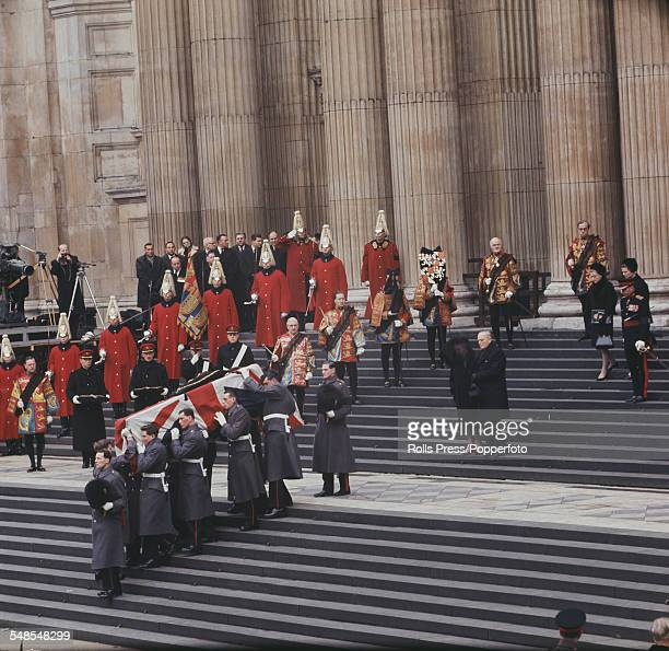 View of members of the British armed services carrying the coffin of Sir Winston Churchill draped in the Union flag down the steps of St Paul's...