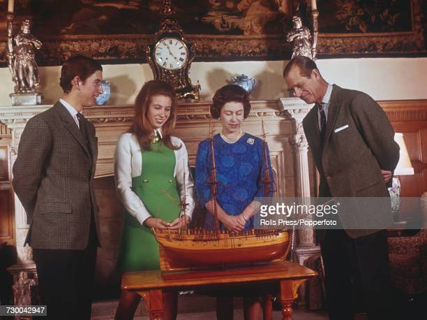 View of members of the British royal family pictured together standing and looking at a model of Captain Cook's ship Endeavour at Sandringham House...