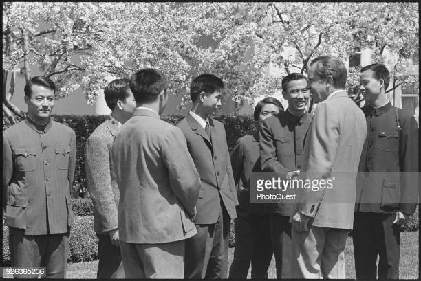 View of members of the Chinese National Table Tennis Team as they shake hands with American politician US President Richard Nixon on the lawn of the...