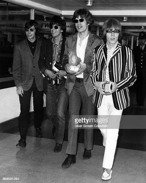 View of members of the English Rock group the Rolling Stones walk through Heathrow Airport London England June 23 1966 Pictured are from left Charlie...