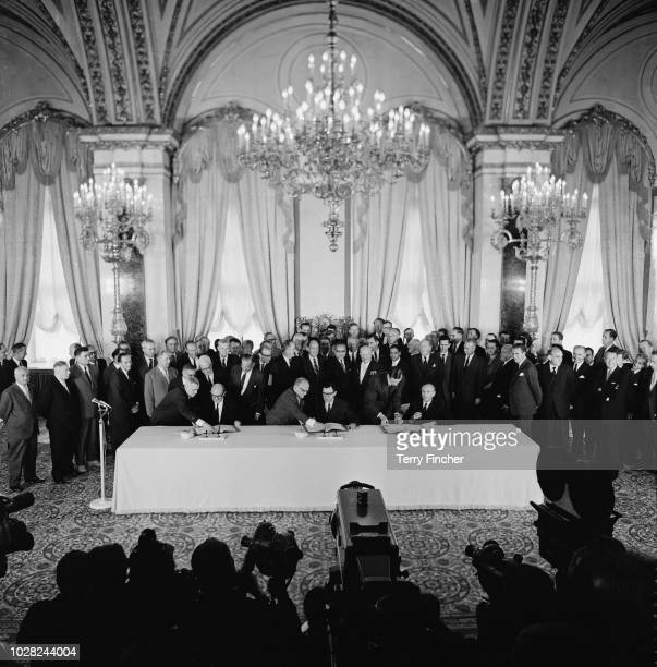 View of members of the governments of the United States, Soviet Union and United Kingdom signing the Partial Nuclear Test Ban Treaty in front of...