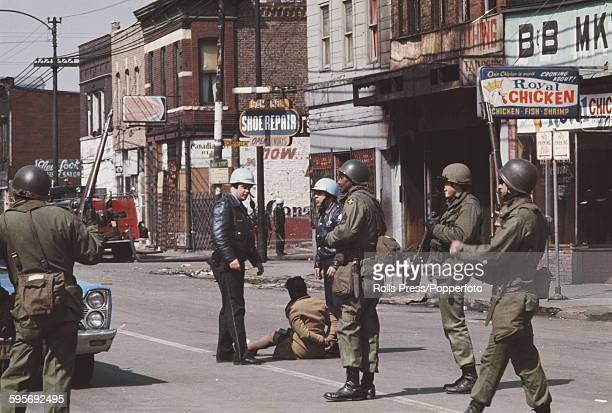 View of members of the Illinois Police Department and members of the National Guard stopping and searching a suspect on a Chicago city street during...