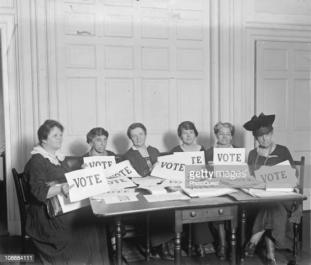 View of members of the National League of Women Voters seated around a table holding signs that read 'VOTE' September 1924