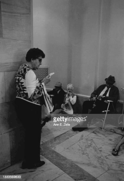 View of members of the public, some reading, as they wait in a hall of the Russell Senate Office Building, Washington DC, October 3, 1973. They were...
