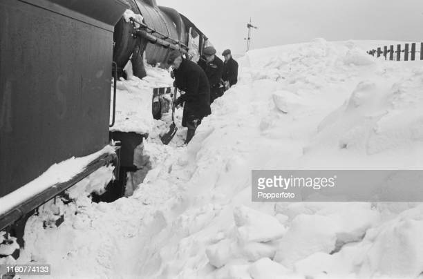 View of members of the train crew and rail workers clearing snow from the wheels of a stranded steam locomotive stuck in a snowdrift near Abington...
