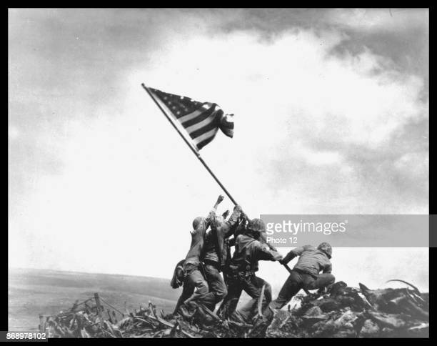 View of members of the United States Marine Corps 5th Division as they raise an American flag on Mount Suribachi during the Battle of Iwo Jima,...