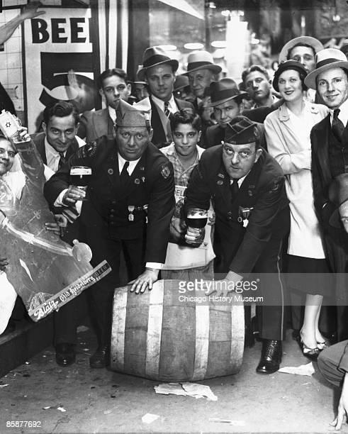 View of men and women celebrating the repeal of Prohibition by rolling down a barrel of alcohol and toasting the 18th Amendment's demise Chicago 1933...