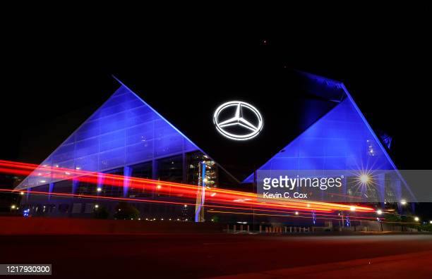 View of Mercedes-Benz Stadium as it is lit up with blue lights on April 09, 2020 in Atlanta, Georgia. Landmarks and buildings across the nation are...