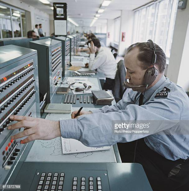 View of Metropolitan Police Officers and civilian staff working and receiving emergency calls in the recently opened new radio room at New Scotland...